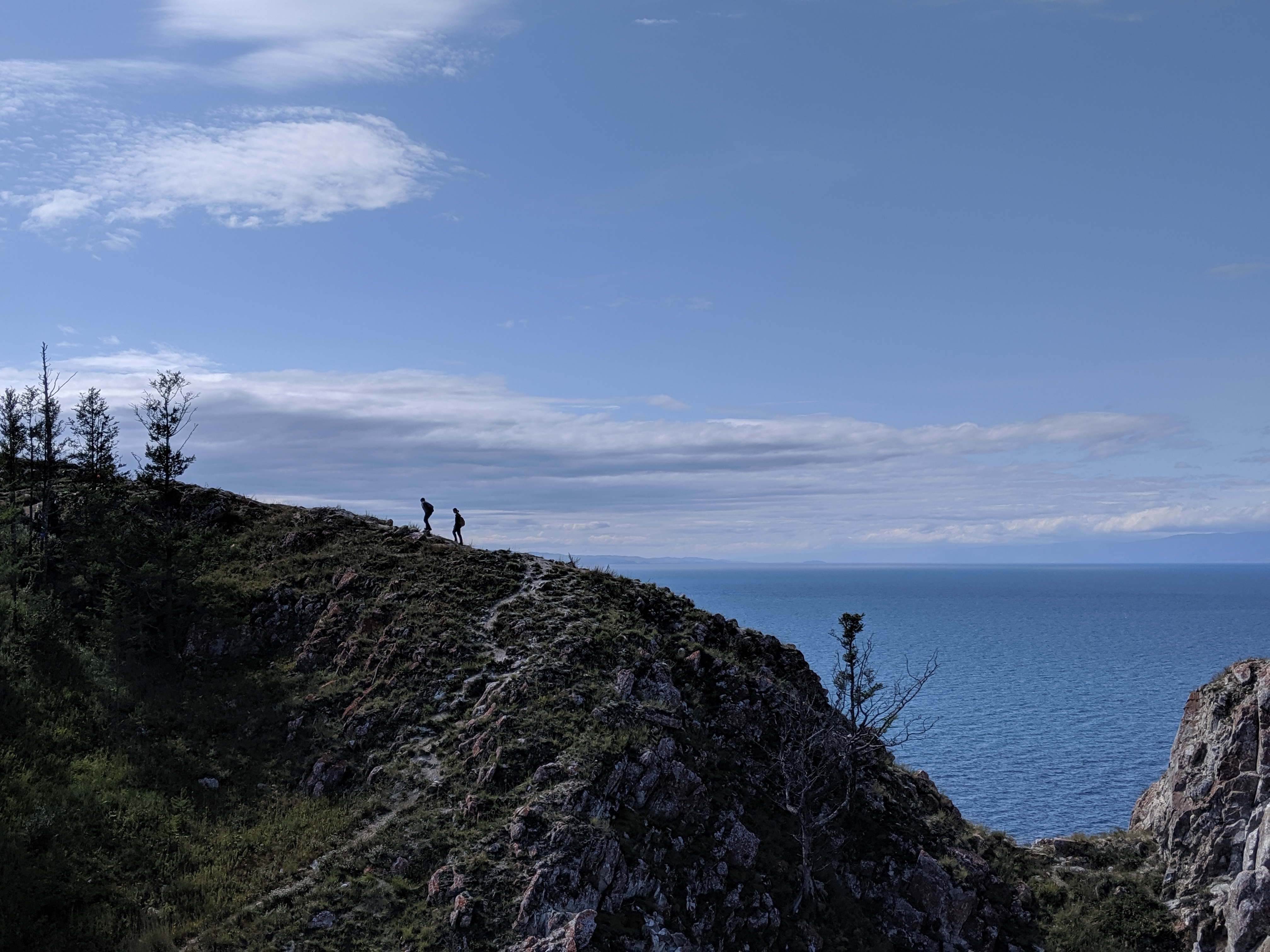 Hikers on a cliff overlooking Lake Baikal on Olkhon Island